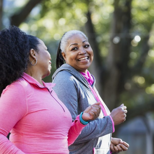 Two African-American women exercising together in the city, jogging or power walking, laughing and conversing. Buildings and trees are out of focus in the background. The one in pink is in her 60s and her friend is in her 50s.